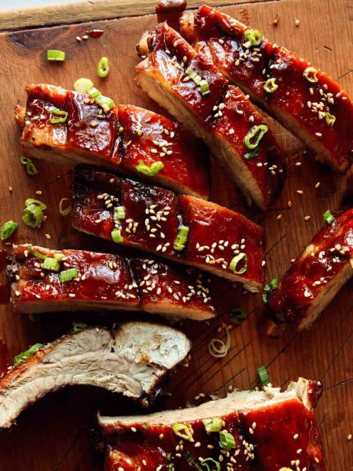 A close up on sticky oven baked ribs on a cutting board, a Super Bowl finger food idea.