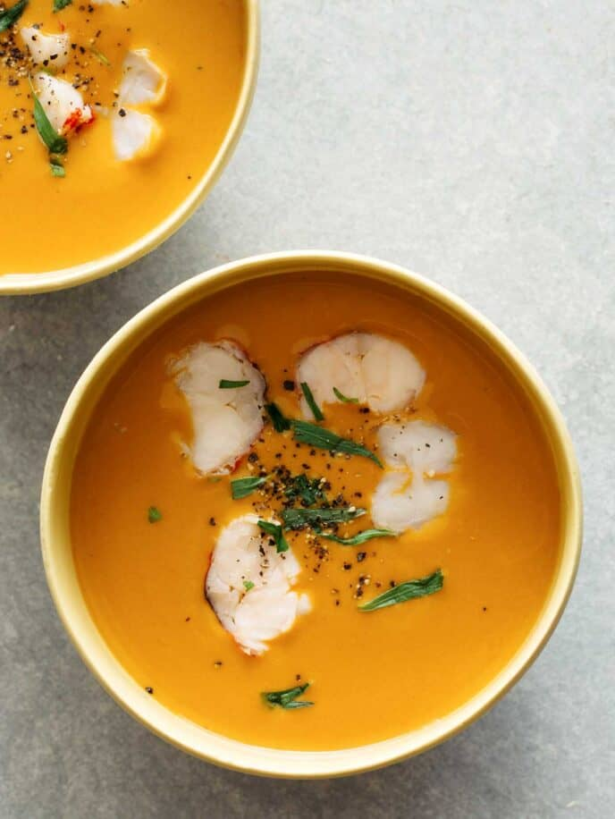 Two bowls of lobster bisque on a surface.