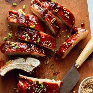 Sticky oven baked ribs being cut on a cutting board.
