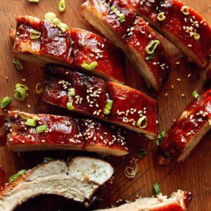 A close up on sticky oven baked ribs on a cutting board.