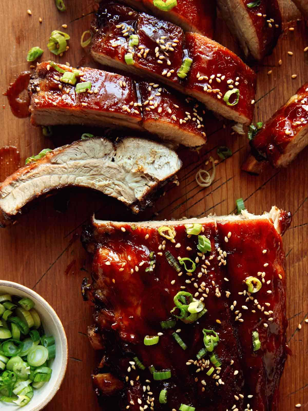 Oven baked sticky ribs on a cutting board.