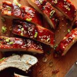 Oven baked sticky ribs with sesame seeds and green onions on a cutting board.