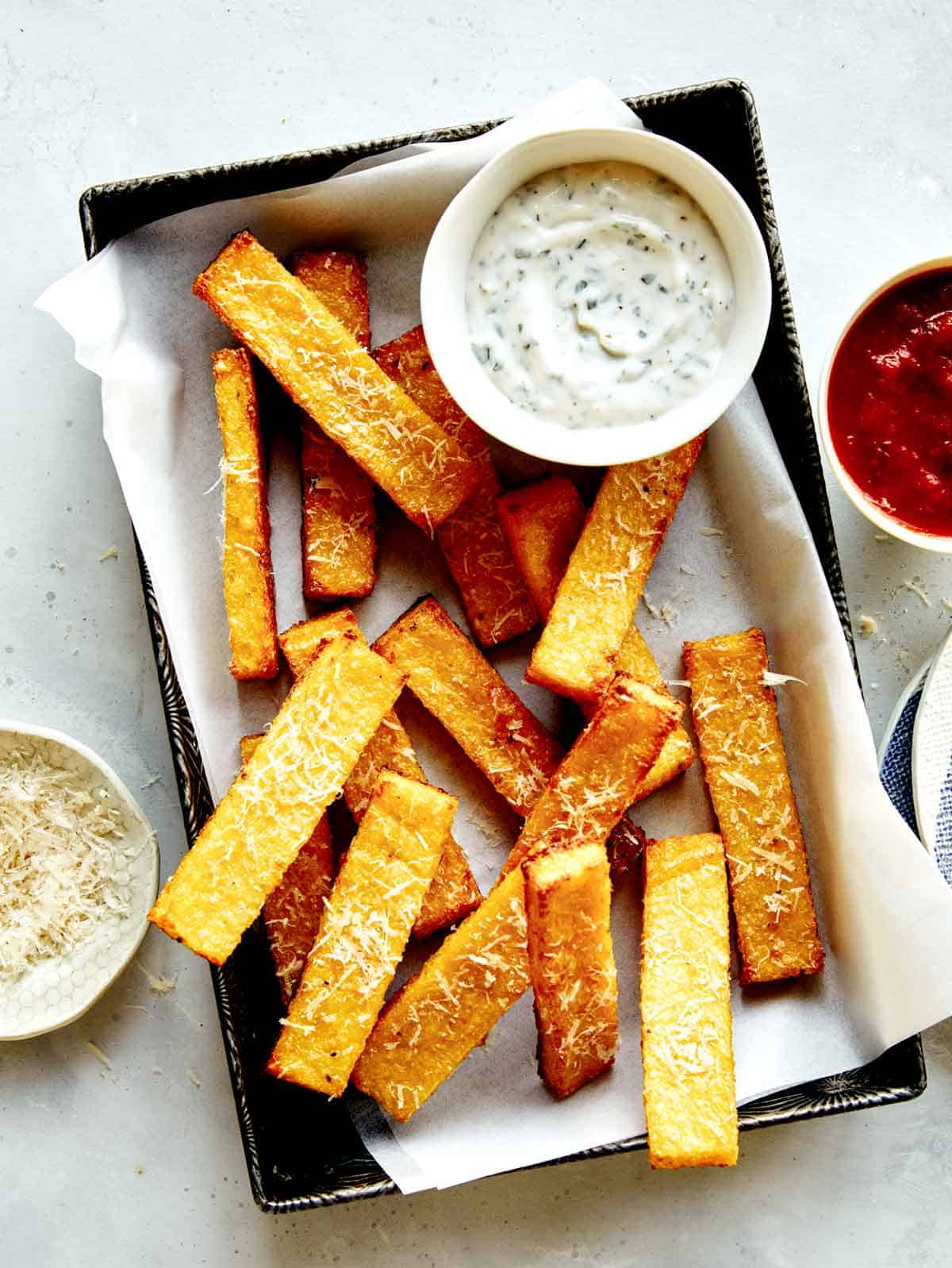 Polenta fries in a basket with dipping sauces next to it.