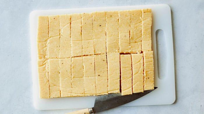 Cooled polenta cut into sticks on a cutting board.