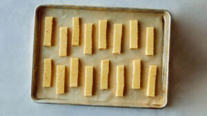 Polenta fries on a baking sheet ready to be baked.