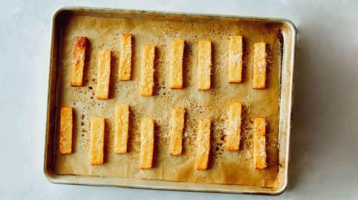 Baked polenta fries sprinkled with parmesan.