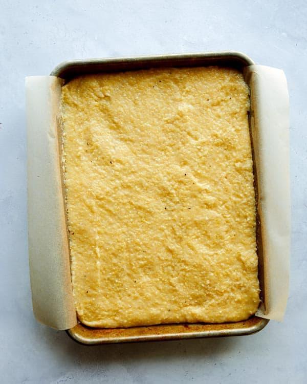 Polenta spread out into a baking sheet.