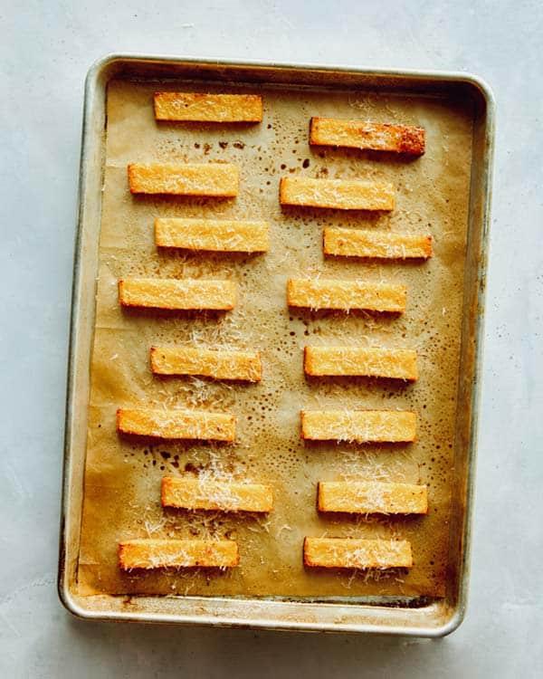 Baked polenta fries on a baking sheet.