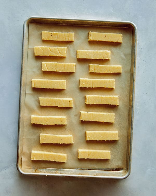 Polenta fries on a baking sheet waiting to be baked.