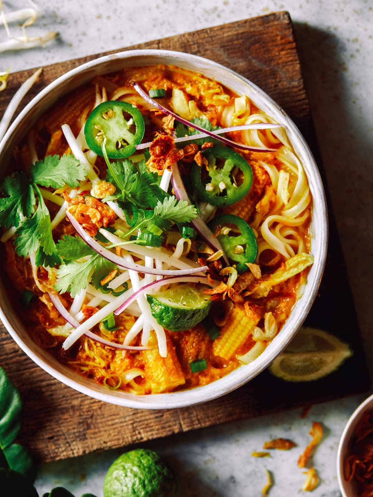 Spicy chicken laksa in a bowl on a cutting board.