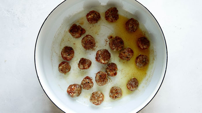 Turkey sausage meatballs seared in a stock pot for tortellini soup.