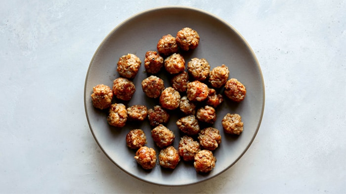 A plate of sausage meatballs on a kitchen counter.