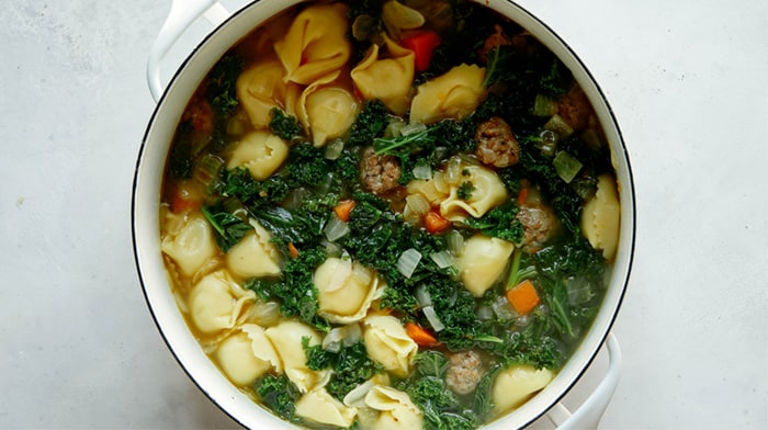 Tortellini soup ready to serve in a stock pot.