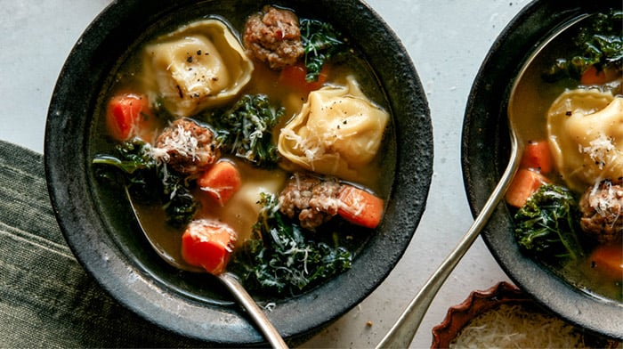Tortellini Soup recipe in two bowls with spoons next to it.