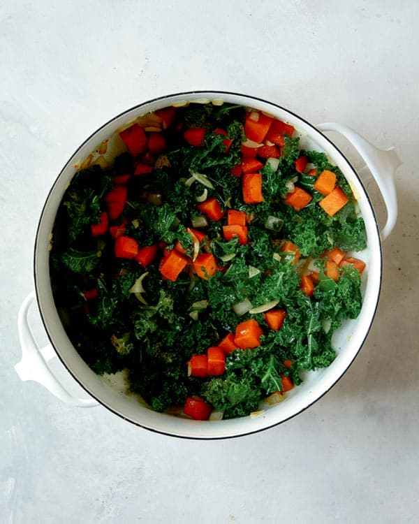 Kale, sweet potatoes, and onions in a stock pot cooking to make tortellini soup.