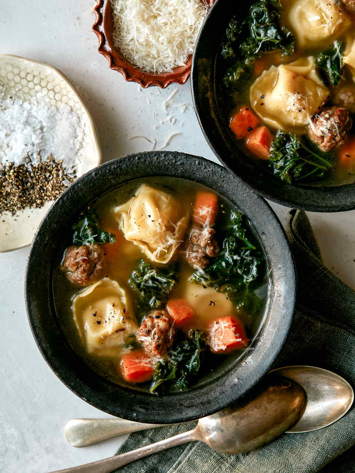 Tortellini Soup recipe in two bowls with parmesan next to it.