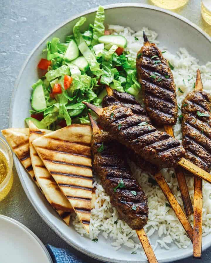 Lamb kofta on rice with pita triangles and salad.