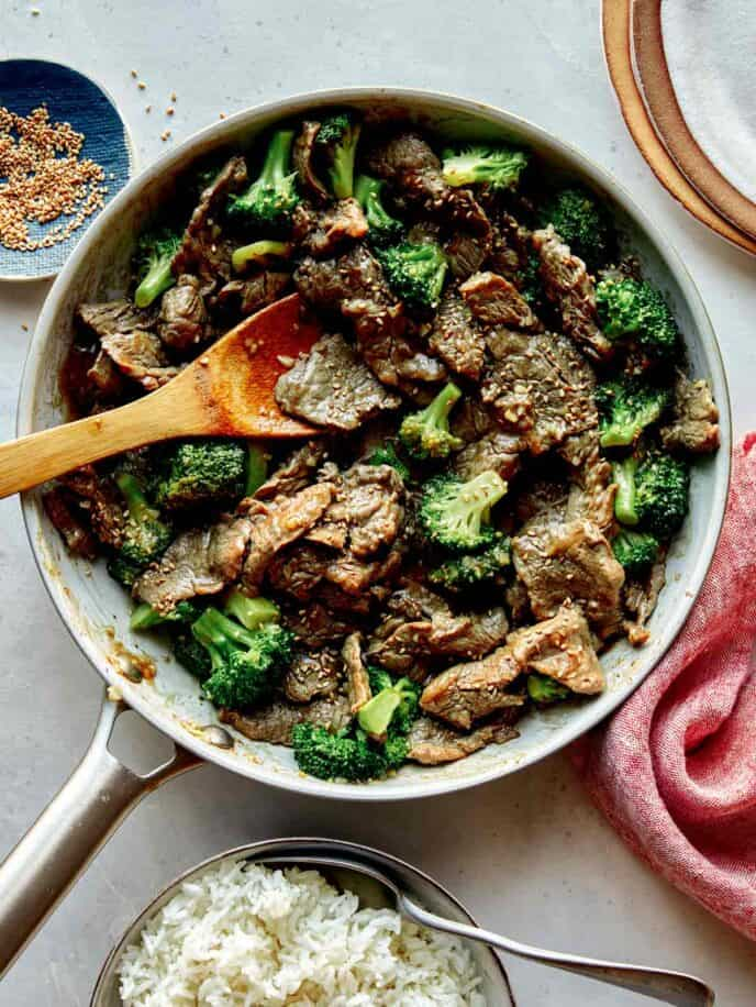 Beef and broccoli in a skillet with plates on the side.