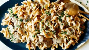 Beef stroganoff plattered with chives and serving utensils.