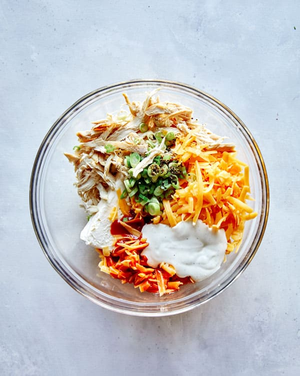 Buffalo chicken dip ingredients in a glass bowl.