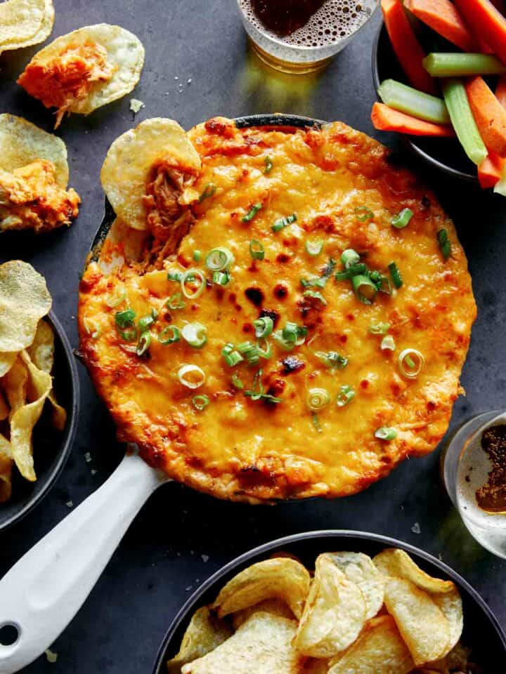 Buffalo chicken dip in a skillet with chips and veggies on the side.