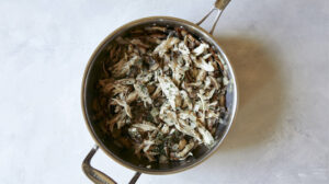 Chicken and mushrooms in a skillet with onions.