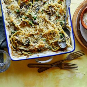 Chicken tetrazzini in a baking dish with a spoon in it.