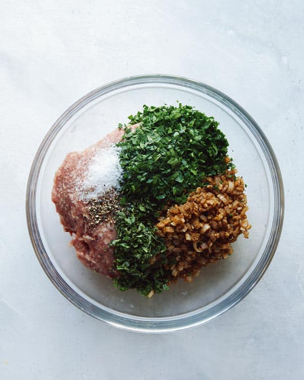 Ground lamb with seasoning in a glass bowl.