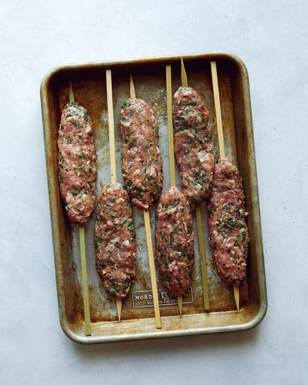 Ground lamb formed onto skewers to be grilled to make Lamb Kofta.