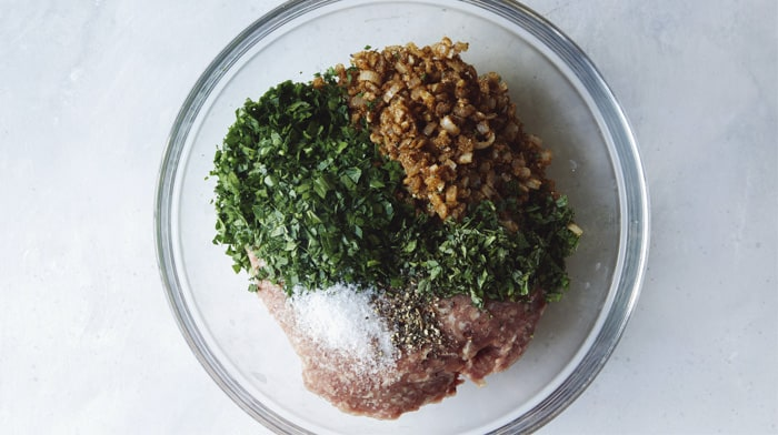 Ground lamb with seasoning in a glass bowl to mix together.