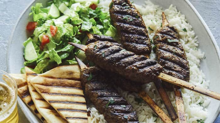 Lamb kofta skewers on a platter with pita and rice.