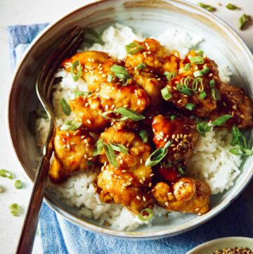 Bowl of sesame chicken on white rice with a fork.