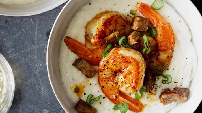 Shrimp and grits in a bowl with green onions on top.