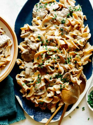 Beef Stroganoff recipe on a platter with chives on top.