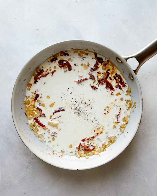 Cream with onions and sun dried tomatoes in a skillet to make Tuscan Chicken.