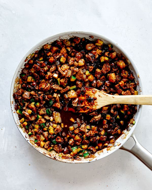 Black bean paste in a skillet mixed with veggies and meat.