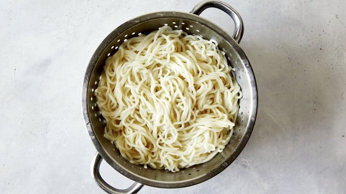 Udon noodles cooked in a colander.