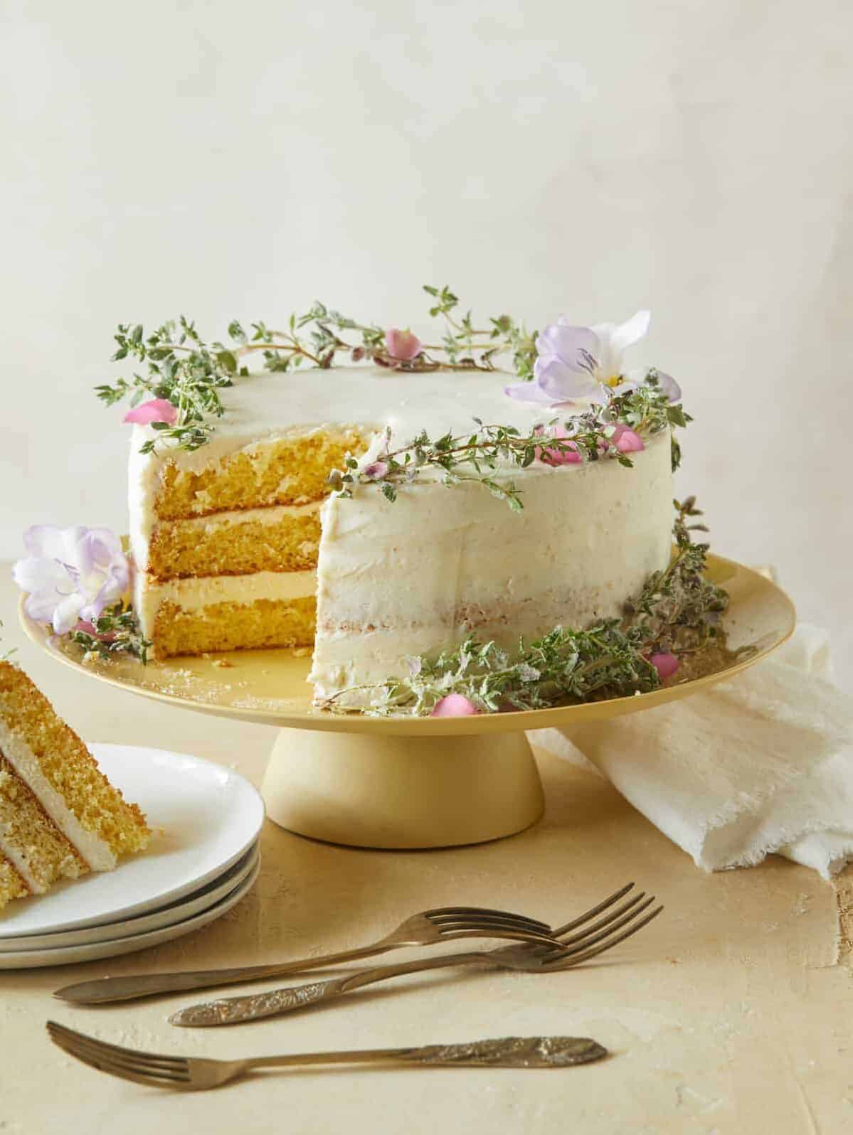 A browned butter cake with vanilla honey frosting with a slice on a plate and forks.