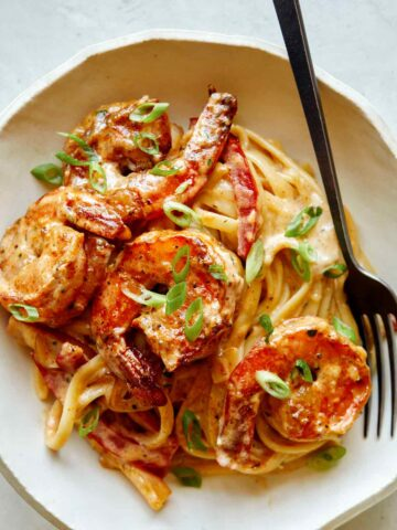 Cajun shrimp pasta recipe in a bowl with a fork on the side.