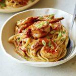A bowl of cajun shrimp pasta recipe with green onions.