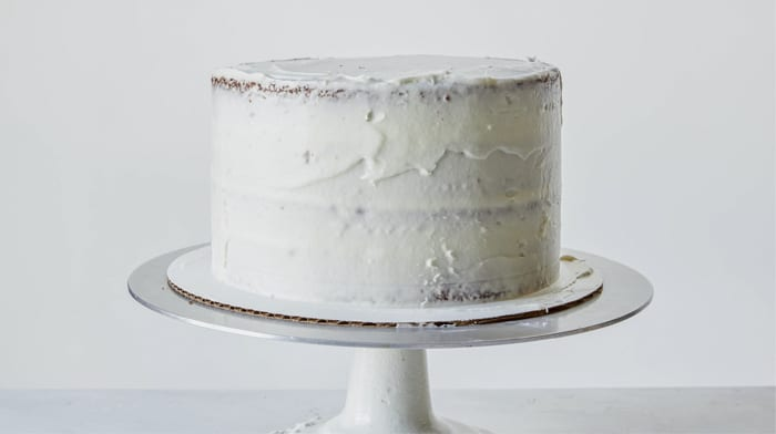 A carrot cake recipe with a crumb coat on it.