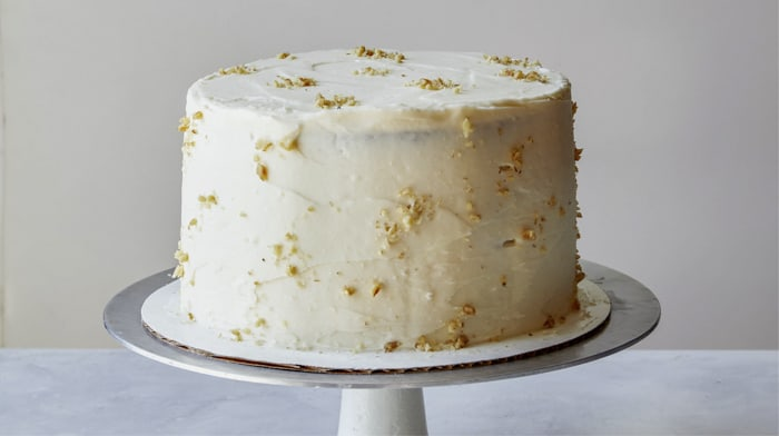 Carrot cake with crushed walnuts on it.