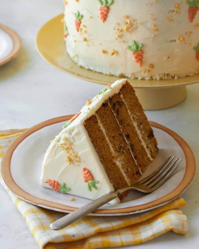 A slice of carrot cake with cream cheese frosting on a plate.