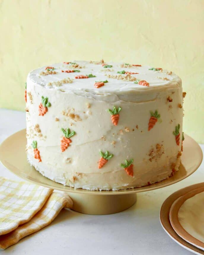 A carrot cake with cream cheese frosting on a plate.