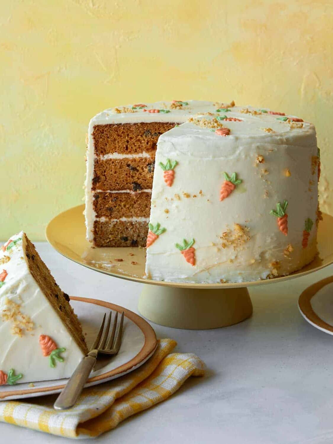 Carrot cake recipe on a cake stand with a slice out.
