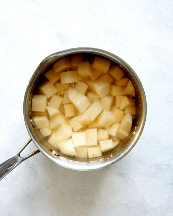 Potatoes being boiled in a pot.
