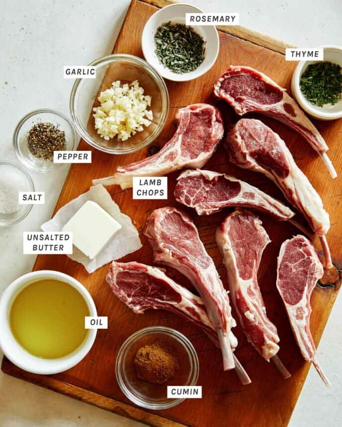 Lamb chops on a cutting board with rub ingredients around them.