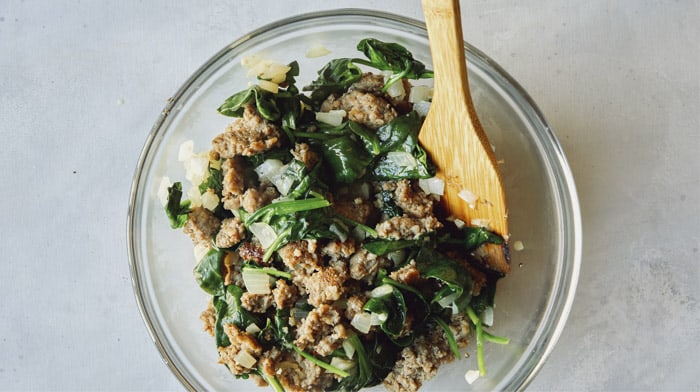 Sausage and spinach and other ingredients for the filling of a strata.