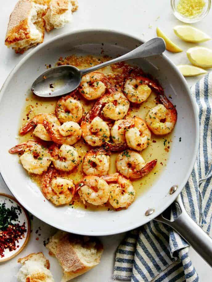 Shrimp scampi in a skillet with lemon wedges.