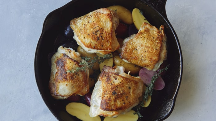Crispy chicken thighs in a skillet with potatoes.